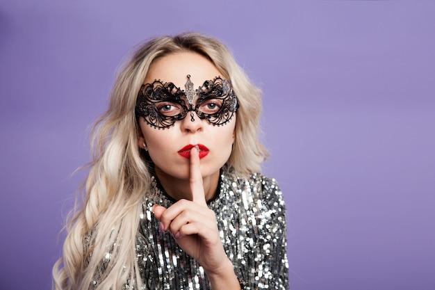 Sexy blonde meisje in kantmasker legde een vinger op haar lippen