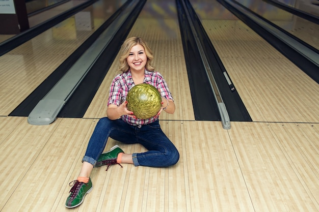 Sexy blonde meisjeszitting met bal op vloer in kegelclub.