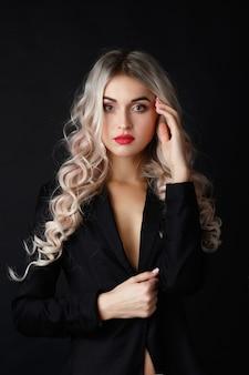 Sexy blonde met lang krullend haar vormt in zwarte jas in een donkere studio