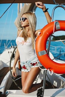 Sexy blonde modelmeisje met slank lichaam in jeansborrels en het witte t-shirt stellen op een jachtschip bij het overzees