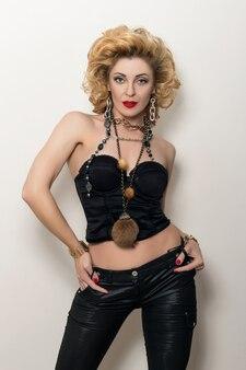 Sexy blonde volwassen vrouw in zwart korset en leerbroeken die op witte achtergrond stellen
