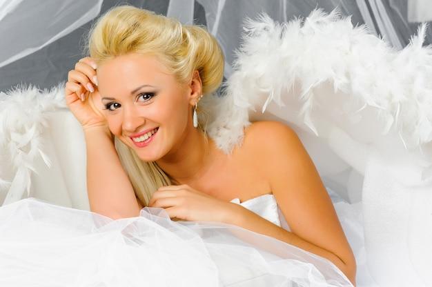 Sexy blonde vrouw in engel kostuum poseren