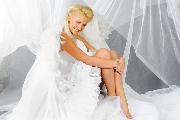 Sexy blonde vrouw in engel kostuum toont haar sexy benen.