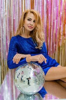 Sexy blonde vrouw in glanzende blauwe jurk poseren met discobal