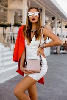Sexy blonde vrouw in grote zonnebril met volle lippen buiten poseren. rood jasje, stijlvolle zilveren accessoires. perfect figuur.