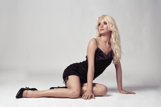Sexy blonde vrouw in jurk poseren in studio