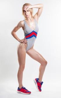 Sexy blonde vrouw in lichaamszwempak geïsoleerd stellen
