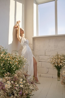 Sexy blonde vrouw in mooie witte jurk staat in de buurt van raam voor een boeket van wilde bloemen