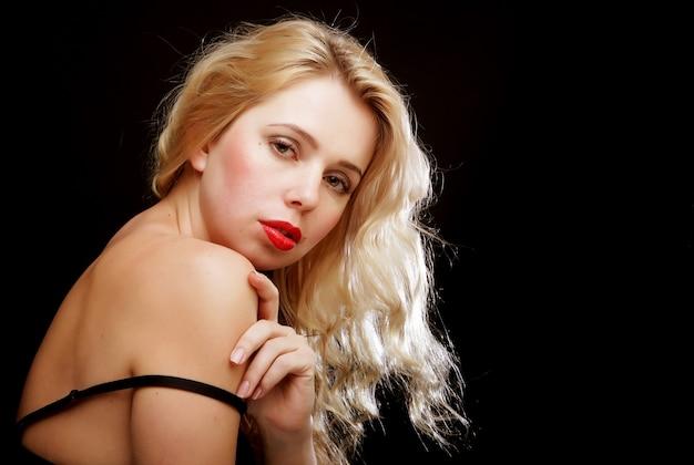 Sexy blonde vrouw met krullend haar in zwarte lingerie