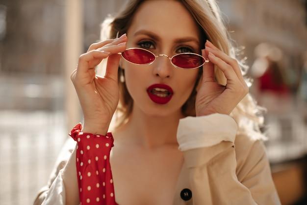 Sexy blonde vrouw met rode lippen zet kleurrijke zonnebril op. aantrekkelijke krullende dame in beige trenchcoat kijkt buitenshuis in de camera