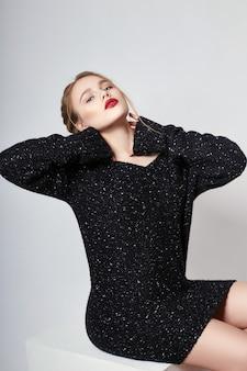 Sexy blondemeisje in sweater levendige make-up
