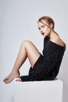 Sexy blondemeisje in sweaterzitting, levendige make-up