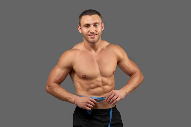 Sexy bodybuilder met meetlint rond de taille.