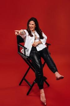 Sexy brandende vrouw in een wit overhemd zit op een zwarte stoel en schreeuwt emotioneel op een rode achtergrond