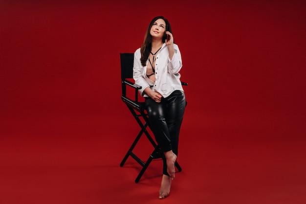 Sexy brandende vrouw in een wit overhemd zittend op een stoel met een rode telefoon op een rode achtergrond