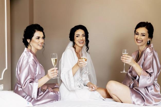 Sexy bruid & bruidsmeisjes springen op bed voor bruiloft