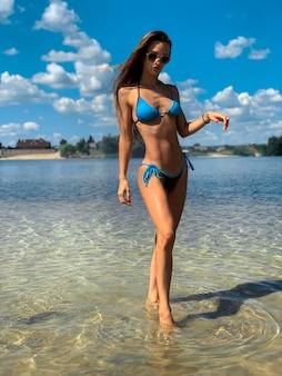 Sexy brunette dame in blauwe zwembroek poseren op het strand in warme zomerdag
