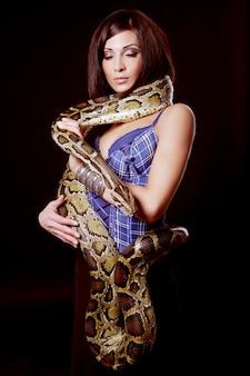 Sexy brunette met python op zwarte achtergrond