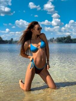 Sexy brunette vrouw in blauwe zwembroek poseren op het strand in warme zomerdag