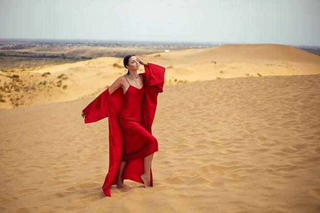 Sexy brunette vrouw in een rode lange jurk staat op een duin in de zomer in dagestan