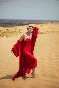 Sexy brunette vrouw in een rode lange jurk staat op een duin in de zomer