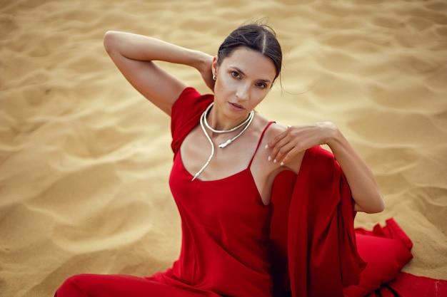 Sexy brunette vrouw in een rode lange jurk zit op een duin in de zomer in dagestan