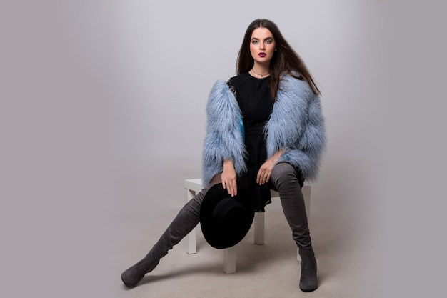 Sexy brunette vrouw in trendy blauw bont jasje en fluweel strakke hoge laarzen poseren op grijze muur.