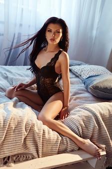 Sexy brunette vrouw in zwarte lingerie thuis op het bed.