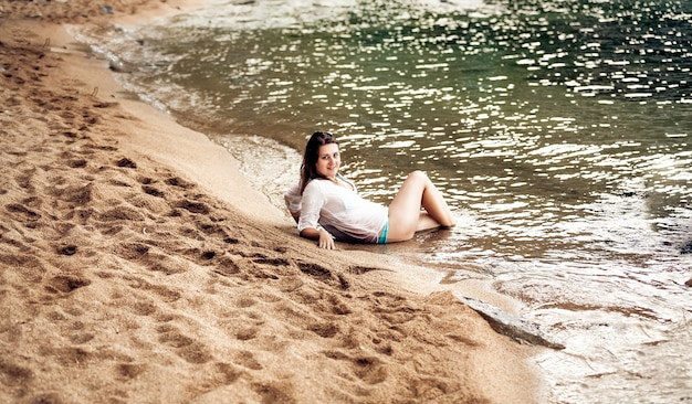 Sexy brunette vrouw liggend op zanderige kust sea