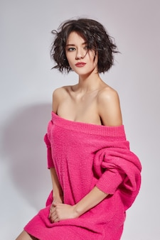 Sexy brunette vrouw met kort haar in een roze trui