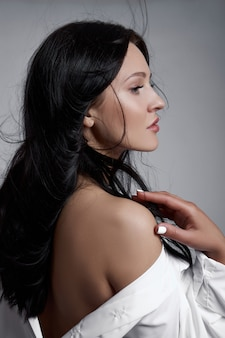 Sexy brunette vrouw met lang haar, perfecte figuur slank lichaam. natuurlijke make-up op het gezicht van een meisje