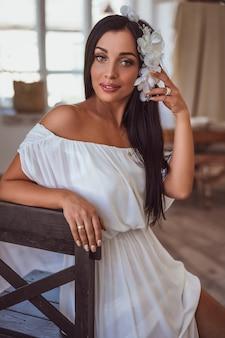 Sexy brunette zit in een witte jurk bij het raam