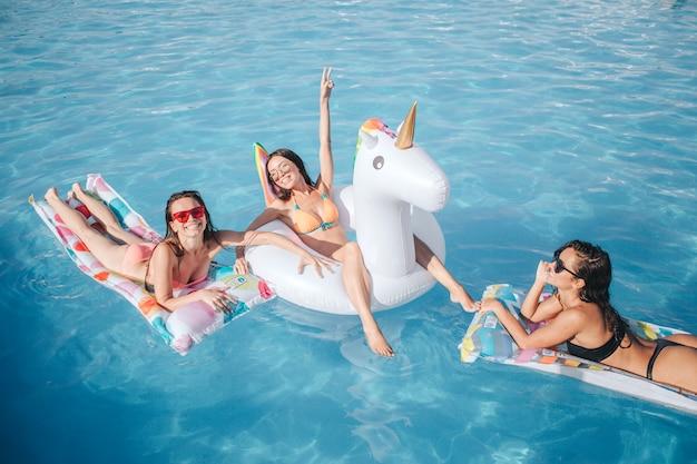 Sexy brunettes die op drijvers in pool zwemmen. ze chillen samen. vrouw in het midden wijst omhoog en glimlachend. andere modellen poseren op camera. ze zijn blij.
