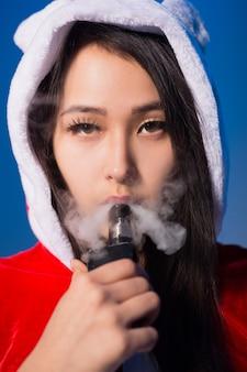 Sexy chinese vrouw in santa claus kostuum elektronische sigaret roken en stoom uitademen