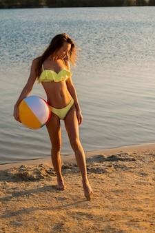 Sexy dame met strandbal in geel zwempak bij zonsondergang