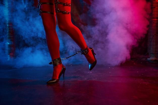 Sexy dame poseert in rode bdsm-kousen, verlaten fabrieksinterieur. jong meisje in erotisch ondergoed, sexfetisj, seksuele fantasie