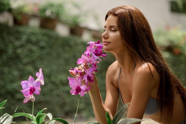 Sexy dame poseren liggend in een kas met bloeiende planten met een roze bloem in haar hand