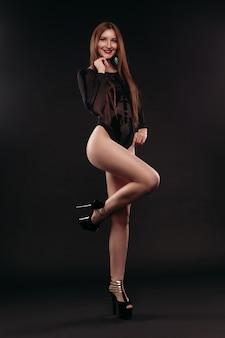Sexy danseres in zwarte meshy body en hoge hakken