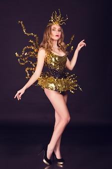 Sexy disco party vrouw gekleed in een uniek gouden kostuum met metalen vleugels. perfect voor stijlvolle club-, disco- en mode-evenementen