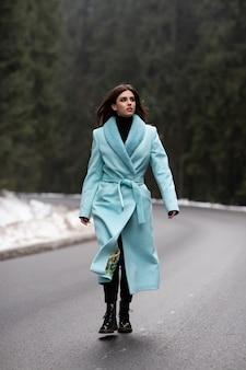 Sexy donkerbruin meisje dat op weg op de winterbergen loopt