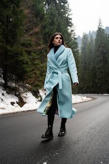 Sexy donkerbruin meisje die op weg op de lijst van de winterbergen lopen. betoverende jonge vrouw, gekleed in stijlvolle blauwe lange jas. mode, zaken en mooie mensen concept ..