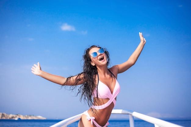 Sexy donkerbruin meisje in wit zwempak op luxe wit jacht.