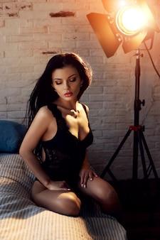 Sexy donkerbruine vrouw in zwarte lingerie thuis op het bed. perfect figuur, mooi lichaam op het meisje. gladde schone huid en lang sterk haar. het meisje in het licht van de gele lamp