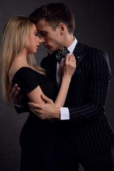Sexy elegant koppel in een tedere passie. mooie vrouw naast een man op een donkere achtergrond.
