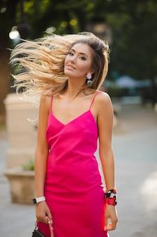 Sexy elegante aantrekkelijke vrouw in roze sexy zomerjurk lang haar wandelen in de straat