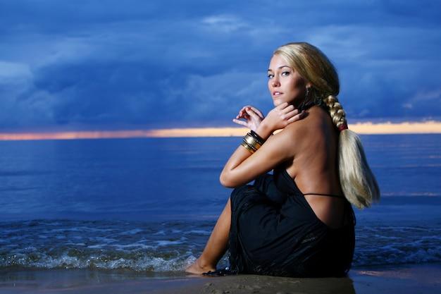 Sexy en luxe vrouw op de zonsondergang