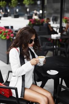 Sexy en modieuze brunette model meisje met professionele make-up en stijlvolle zonnebril, in witte korte broek en in een witte jas zit met een kopje koffie en met rode clutch bag aan tafel in café