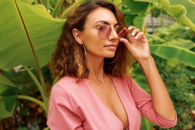 Sexy europese vrouw met krullende haren in roze jurk staande over palmbomen.