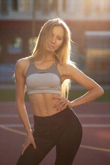 Sexy fit model met getraind lichaam in sportkleding die zich voordeed op een tennisbaan in zonnestralen. vrouwelijk fitnessconcept