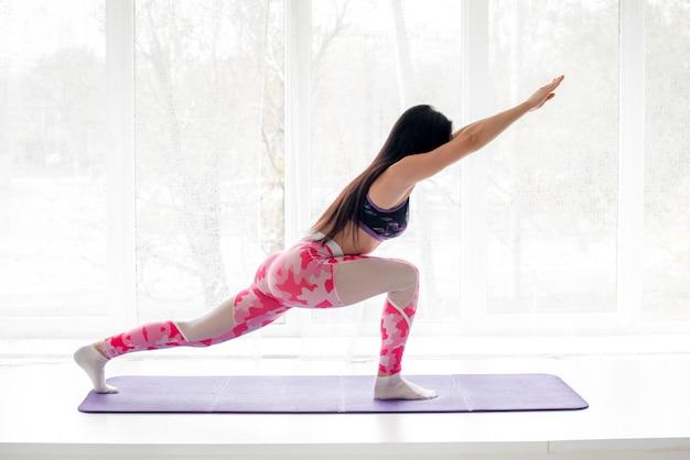 Sexy fitness atleet voert oefeningen uit op de billen in de studio. body-building